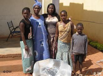 woman and children around a solar cooker