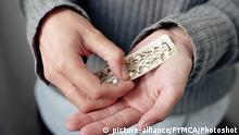 Woman opens packet of contraceptive pills in hands  