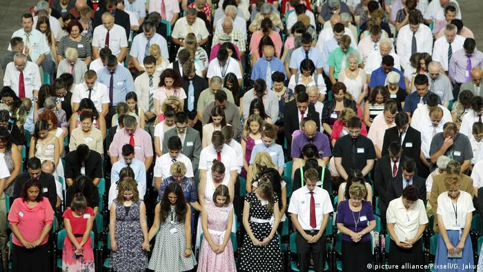 People dressed neatly pray together international conference of Jehovah's Witnesses in Croatia