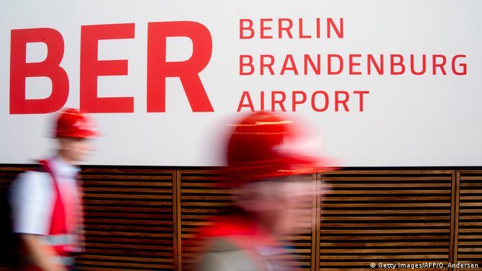 Рабочие в касках на фоне логотипа аэропорта BER