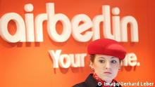 An Air Berlin Flight attendant in front of company logo (imago/Gerhard Leber)