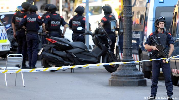 Armed policemen stand in a cordoned off area