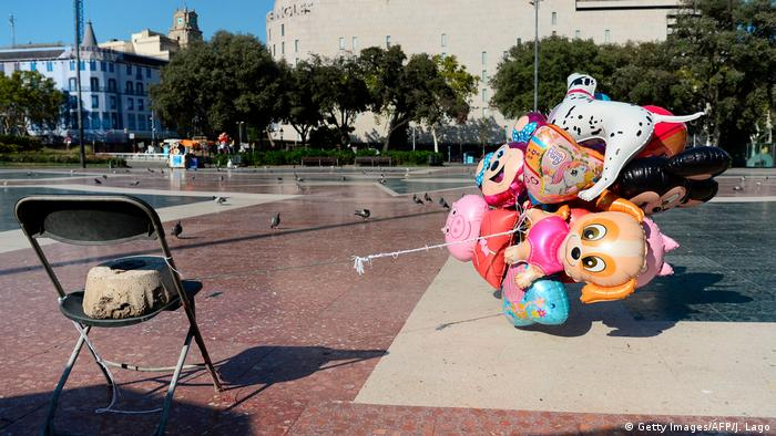 Abandoned air balloons of a street vendor tied to a chair fly at the empty Plaza de Catalunya
