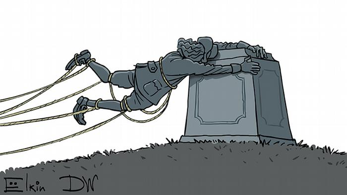 Памятник солдату стаскивают с постамента, за который солдат цепляется