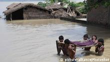 (170817) -- SITAMARHI (INDIA), Aug. 17, 2017 () -- Villagers carrying a patient wade through a flooded road in Sitamarhi, India's eastern state of Bihar, on Aug. 17, 2017. The floods in India's eastern state of Bihar killed at least 91 people and affected over 9.6 million others, officials said Wednesday. (/Stringer) |
