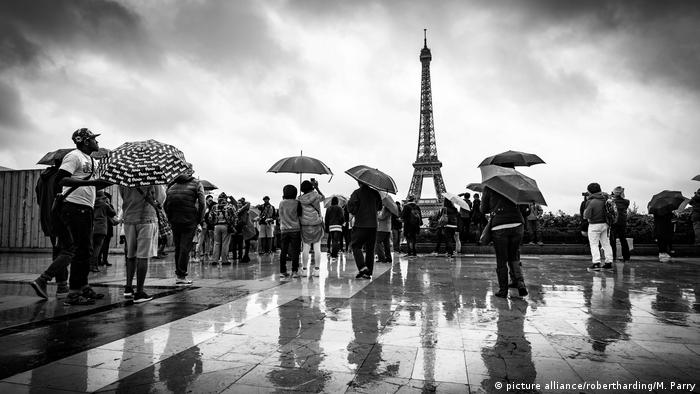 People with umbrellas walk in front of the Eiffel tower