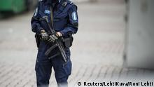 Police stand guard following a knife attack in the Finnish city of Turku.