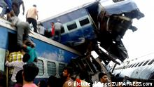 Rail car lays atop another derailed car after a deadly train derailment in the Indian state of Uttar Pradesh