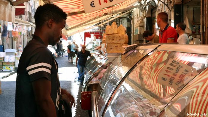 Karamo Caseey buys food at the market in Catania (DW/D.Pundy)