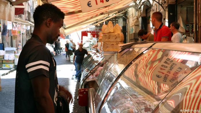 Karamo Caseey buys food at the market in Catania