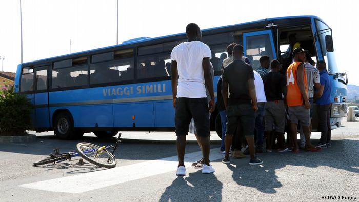 Migrants in Italy prepare to board a bus in Mineo