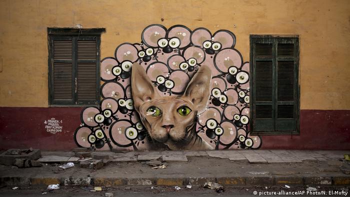 Lukisan dinding menunjukkan wajah kucing dengan tikus mengintip dari belakang