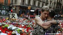 21.08.2017****Two men react at an impromptu memorial where a van crashed into pedestrians at Las Ramblas in Barcelona, Spain August 21, 2017. REUTERS/Susana Vera