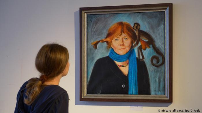 Uma visitante olha a pintura de Angela Merkel com cabelos e manta no pescoço lembrando a popular figura Píppi Meiaslongas,