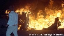 Ein Mann steht am 27.08.1992 vor brennenden Pkw auf einer Straße am zentralen Asylbewerberheim von Mecklenburg-Vorpommern in Rostock-Lichtenhagen. Vom 22. bis 28. August 1992 randalierten bis zu 1.200 meist jugendliche rechtsradikale Gewalttäter vor dem Zentralen Asylbewerberheim Mecklenburg-Vorpommern in Rostock-Lichtenhagen. Unter dem Beifall von bis zu 3000 Schaulustigen und vielen Fernsehkameras bewarfen die Rowdies das überwiegend mit Rumänen belegte Hochhaus (Sonnenblumenhaus) sowie die Polizisten mit Steinen und Brandsätzen. Foto: Bernd Wüstneck | Verwendung weltweit
