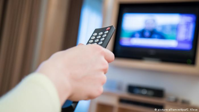 A hand on a TV remote, screen in the background (picture-alliance/dpa/C. Klose)