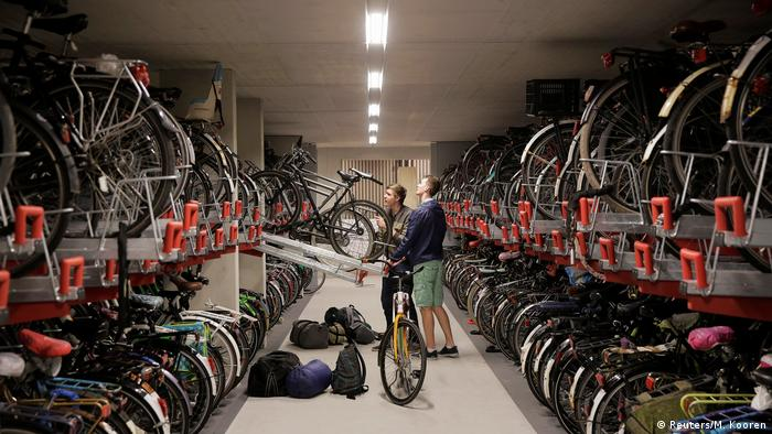 Two men put their bikes on a rack