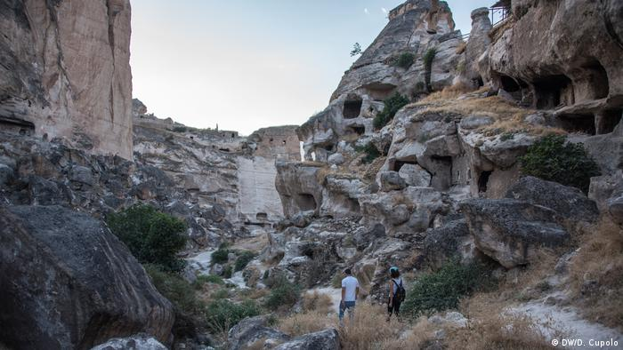 Tourists walk through a valley lined with prehistoric caves in Hasankeyf