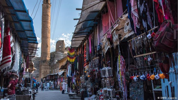 A minaret towers over a market street in Hasankeyf, Turkey