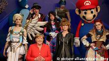 Bundeskanzlerin Angela Merkel (M, CDU) steht am 22.08.2017 in Köln (Nordrhein-Westfalen) unter Cosplayern. Bundeskanzlerin Angela Merkel eröffnet die Computerspielemesse Gamescom (22. bis 26.08.2017). Foto: Oliver Berg/dpa | Verwendung weltweit