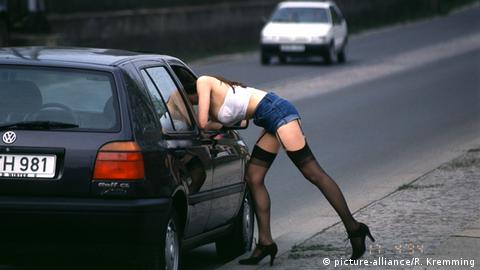 A woman wearing revealing clothing leans into a car (picture-alliance/R. Kremming)