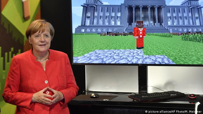 German chancellor Angela Merkel standing beside a Minecraft game, showing her in front of the German Reichstag, during the Gamescom fair for computer games in Cologne, Germany, (picture-alliance/AP Photo/M. Meissner)