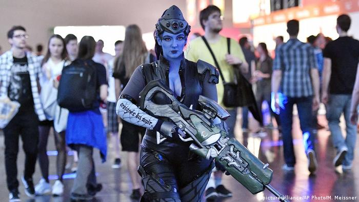 A cosplayer dressed as the fantasy figure Widowmaker from the videogame Overwatch walks with a play gun at the Gamescom fair for computer games in Cologne (picture-alliance/AP Photo/M. Meissner)