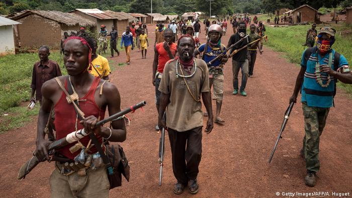 Eine Gruppe Männer mit Gewehren in den Händen marschiert durch ein Dorf