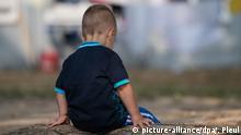 Ein Kind aus Albanien sitzt auf dem Gelände der Erstaufnahmestelle in Eisenhüttenstadt