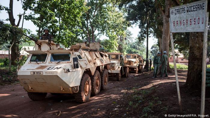 Weiße Panzerfahrzeuge mit der Aufschrift UN fahren durch ein Flüchtlingslager