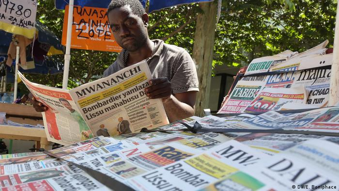 A man reads a newspaper at a newspaper stand in Tanzania