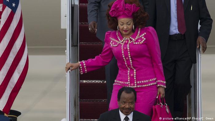 Cameroon's First Lady Chantal Biya, wearing a glitzy magenta two-piece outfit, matching headwrap and handbag, steps off a plane behind her husband President Paul Biya