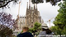 ARCHIV - Touristen sitzen am 20.08.2017 während einer Messe zum Gedenken der Opfer des Terroranschlags vor der römisch-katholischen Basilika La Sagrada Familia in Barcelona (Spanien). Fünf Tage nach den Anschlägen in Spanien hat die Staatsanwaltschaftfür die vier lebend gefassten mutmaßlichen Mitglieder der Terrorzelle Untersuchungshaft beantragt. Zumindest einer der Verdächtigen soll gestanden haben, dass die Gruppe größere Sprengstoffanschläge unter anderem auf die weltberühmte Basilika Sagrada Familia in Barcelona geplant habe, berichteten die Zeitung «El Mundo» und andere Medien. Foto: Matthias Balk/dpa +++(c) dpa - Bildfunk+++ | Verwendung weltweit