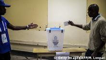 TOPSHOT - An Angolan voter prepares to cast his ballot at a polling station in Luanda, on August 23, 2017 during general elections. Polling stations opened across Angola in an election that marks the end of President Jose Eduardo Dos Santos's 38-year reign, with his MPLA party predicted to retain power. / AFP PHOTO / MARCO LONGARI (Photo credit should read MARCO LONGARI/AFP/Getty Images)
