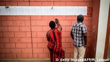 TOPSHOT - Voters check their names against the voters roll at a polling station in Bairo Popular in Luanda, on August 23, 2017. Angolans voted on August 23 in an election marking the end of current President's 38-year reign, with his MPLA party set to retain power despite an economic crisis. / AFP PHOTO / MARCO LONGARI (Photo credit should read MARCO LONGARI/AFP/Getty Images)