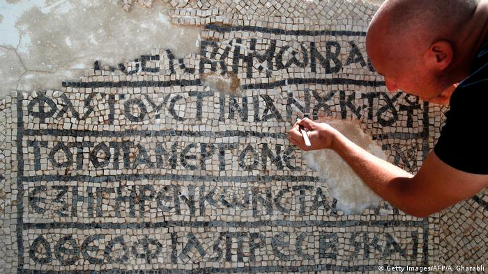 A hands restores a Byzantine mosaic with Greek writing
