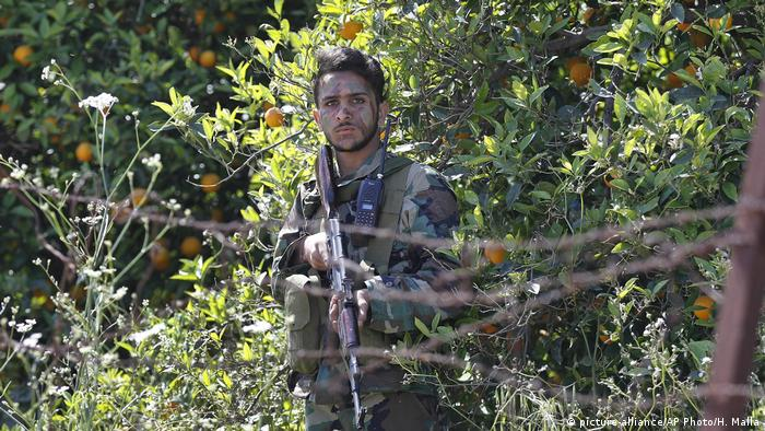 A Hezbollah fighter on the border town of Naqoura, where border negotiations are expected to begin on October 14.