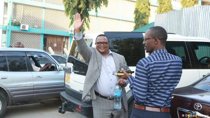 Tundu Lissu, with another man,waves to the camera