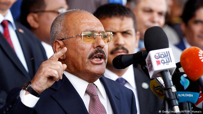 Yemen's Ex-President Ali Abdullah Saleh gestures during a speech before a bank of microphones.