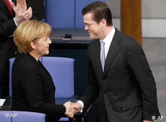 Guttenberg shaking hands with Angela Merkel