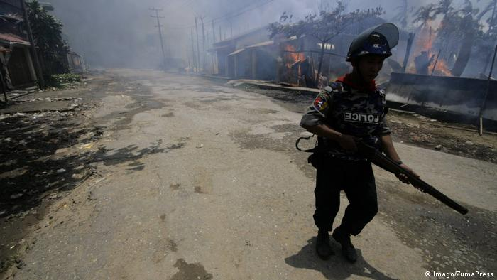 A member of the Myanmar Police Force in a village surrounded by houses set ablaze