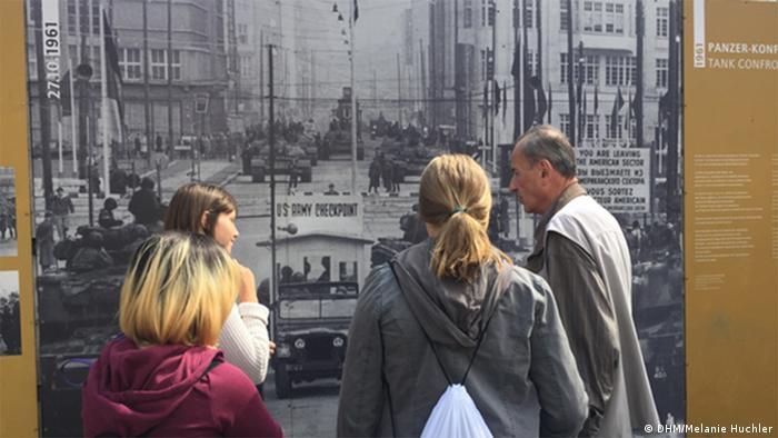 Jugendliche stehen vor einem Plakat mit einer historischen Maueransicht.