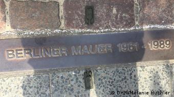 Schriftzug auf einem Stahlband - hier verlief die Berliner Mauer