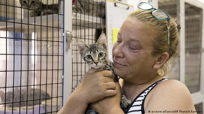 A woman holds a cat before Hurricane Harvey makes landfall
