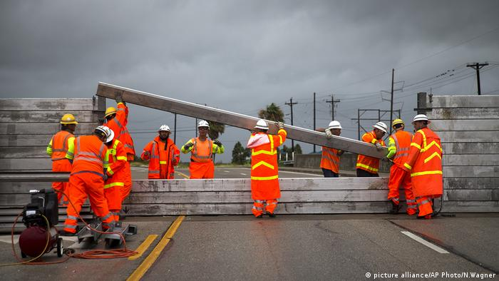 crews install the final portion of a surge wall