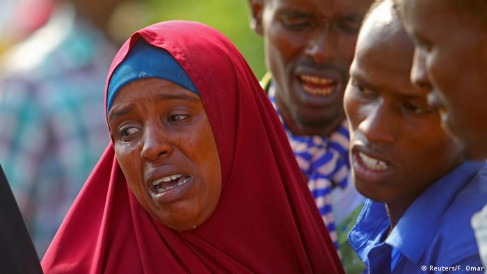 A Somali woman, her face framed by a red hijab, cries for a killed relative.
