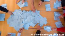 ballot slips on a table, hands reaching for them