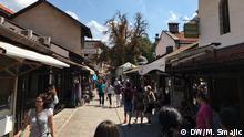 Titel: Sarajevo Schlagworte: Bosnien, Sarajevo, Zentrum, Bascarsija, Leute in Sarajevo, Menschen Wer hat das Bild gemacht?: Mehmed Smajic /DW Bosnisch Wann wurde das Bild gemacht?: August 2017 Wo wurde das Bild aufgenommen? Sarajevo Die Baščaršija ist ein Basar und das historische Stadtzentrum der bosnischen Hauptstadt Sarajevo. Sie wurde im 15. Jahrhundert angelegt. In der Baščaršija befinden sich viele wichtige historische Bauwerke, wie zum Beispiel die Gazi-Husrev-Beg-Moschee oder die Sahat Kula (Uhrturm). Heutzutage ist die Baščaršija die Hauptattraktion für Touristen in Sarajevo.