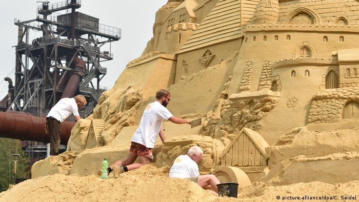Sand artists sculpt a giant sand castle in Duisburg