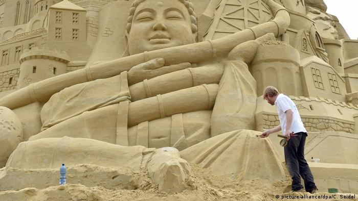 A sand sculptor works on the Duisburg attempt at the world's tallest sandcastle